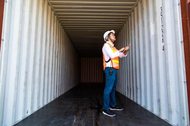 Concept d'assurance maritime et transporteur. ingénieur vérifiant l'intérieur de la boîte des conteneurs au port d'expédition. logistique commerciale concept d'importation et d'exportation.