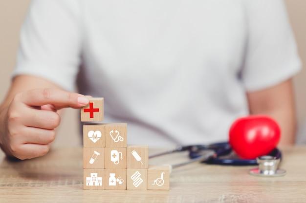 Concept d'assurance santé, main organisant l'empilement de blocs de bois avec l'icône soins médicaux.