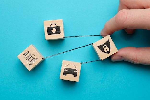 Concept d'assurance voiture, santé, immobilier - panneaux abstraits sur des cubes en bois avec un espace bleu.