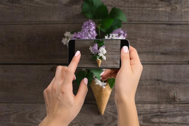 Concept d'atelier de blogs de photographe. main tenant le téléphone et prenant une photo de fleurs. lilas sur fond rustique en bois. espace pour le texte. bonjour printemps