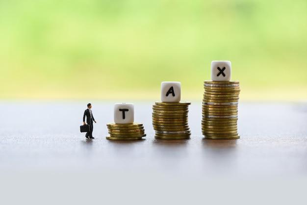 Concept d'augmentation fiscale et finances homme d'affaires et pièces empilées