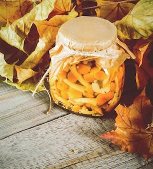 Concept d'automne. aliments conservés dans un bocal en verre sur planche de bois. champignons marinés