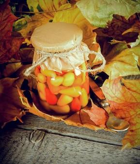 Concept d'automne. aliments conservés dans un bocal en verre sur planche de bois. piment mariné