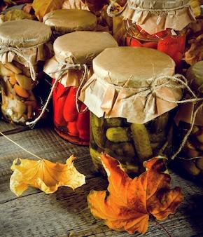 Concept d'automne. aliments conservés dans des bocaux en verre sur planche de bois. nourriture marinée