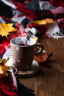 Concept d'automne automne avec couverture tricotée et thé chaud aux baies, feuille d'automne