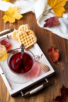 Concept d'automne automne avec couverture tricotée et thé chaud avec gaufres, confiture, miel