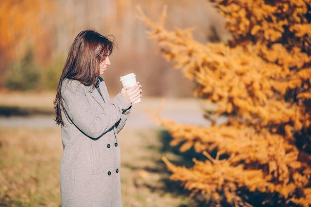 Concept de l'automne - belle femme buvant du café en automne parc sous le feuillage