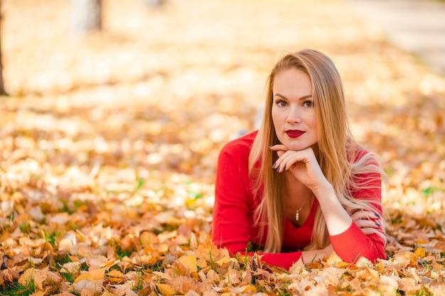 Concept de l'automne - belle femme buvant du café dans un parc en automne sous le feuillage d'automne