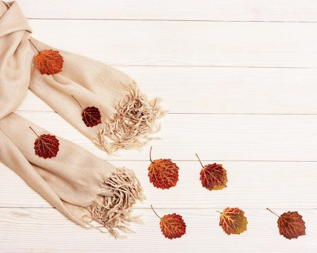 Concept d'automne, les feuilles de tremble rouge volent après une écharpe beige sur fond en bois clair. automne, composition d'automne.