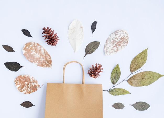 Concept d'automne minimaliste. feuilles séchées, fleurs de pin, sacs en papier isolés sur fond de papier blanc