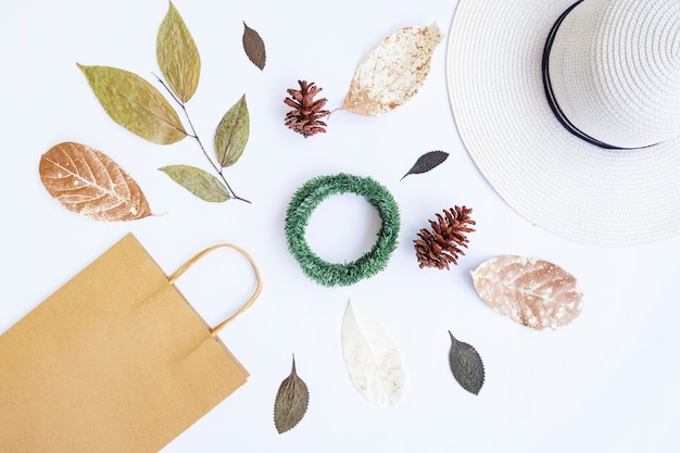 Concept d'automne minimaliste. sac en papier, chapeau blanc, corde de ruban, feuilles séchées, fleurs de pin, couronne de krans isolée sur fond de papier blanc. concept de noël minimaliste