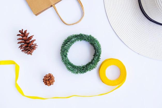 Concept d'automne minimaliste. sac en papier, chapeau blanc, corde de ruban, fleurs de pin, couronne de krans isolée sur fond de papier blanc. concept de noël minimaliste