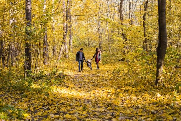 Concept d'automne, de nature et de famille - famille heureuse marchant dans le parc d'automne