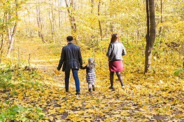 Concept d'automne, de nature et de famille - famille marchant dans le parc d'automne, vue arrière
