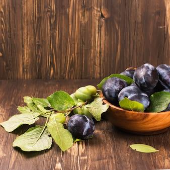 Concept d'automne ou de récolte: bol en bois rempli de prunes mûres.