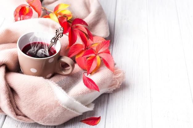 Concept de l'automne. une tasse de thé en bonne santé dans les feuilles rouges jaunes avec une écharpe beige