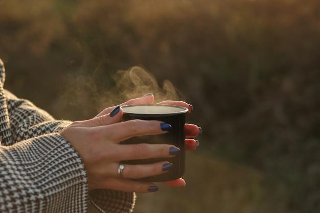 Concept d'automnecafé chaud à la mainune tasse de chocolat chaud dans les mains à l'automnecafé chaud avec