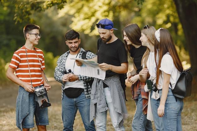 Concept d'aventure, de randonnée et de personnes. groupe d'amis souriants dans une forêt. homme avec une carte.