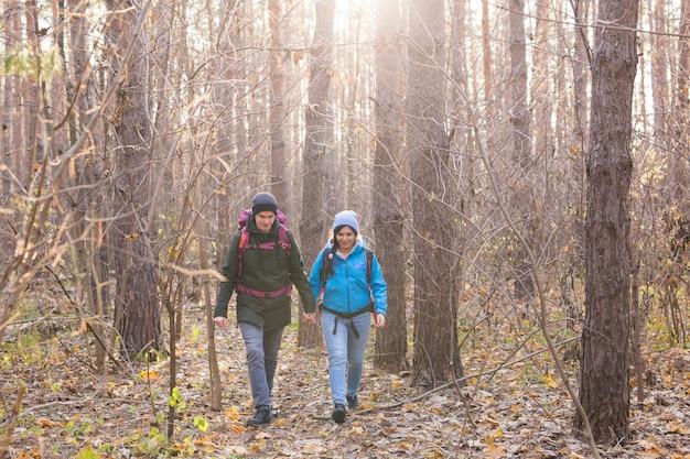Concept d'aventure, de voyage, de tourisme, de randonnée et de personnes - couple souriant marchant avec des sacs à dos sur fond naturel.