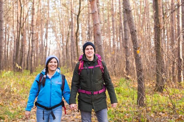 Concept d'aventure, de voyage, de tourisme, de randonnée et de personnes - couple souriant marchant avec des sacs à dos sur