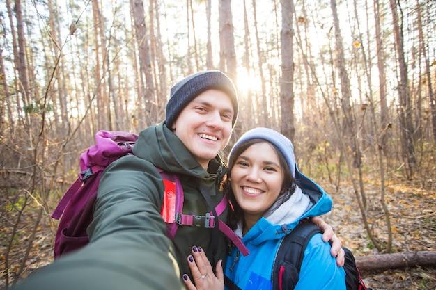 Concept d'aventure, de voyage, de tourisme, de randonnée et de personnes - couple souriant de touristes prenant selfie