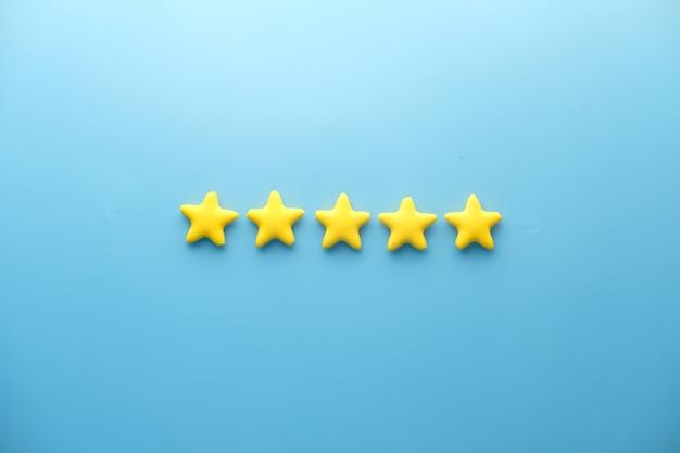 Concept d'avis client. évaluation des étoiles dorées sur fond bleu