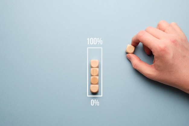 Concept de barre de chargement de zéro à 100 pour cent avec des cubes en bois.