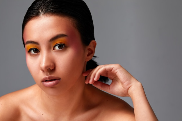 Concept de beauté, une belle femme asiatique avec une peau saine et belle sur fond émeraude.