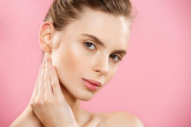 Concept de beauté - belle femme caucasienne avec une peau propre, un maquillage naturel isolé sur un fond rose brillant avec un espace de copie.