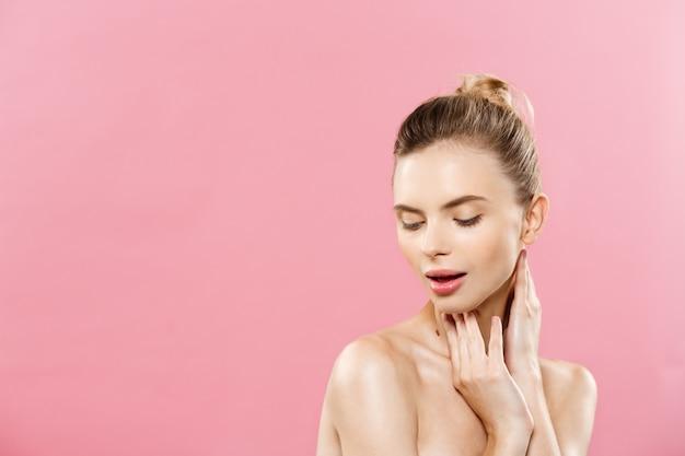 Concept de beauté - belle femme avec une peau propre et fraîche sur le studio rose. visage de soins de la peau. cosmétologie.