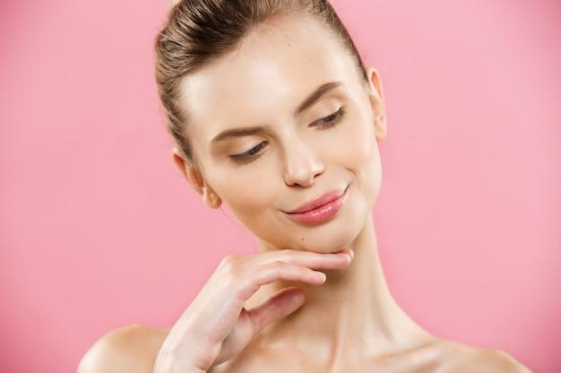 Concept de beauté - close up portrait d'une fille caucasienne attrayante avec une peau naturelle de beauté isolée sur fond rose avec un espace de copie.