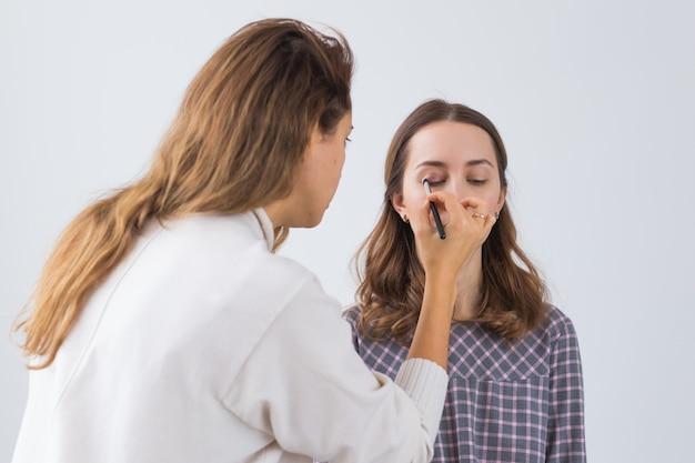 Concept de beauté et cosmétiques - maquilleur faisant professionnel de la jeune femme