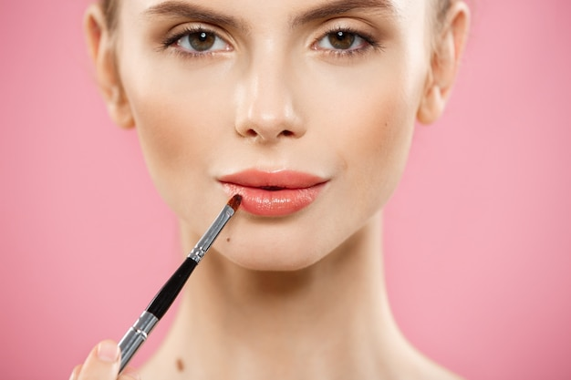 Concept de beauté - femme appliquant un rouge à lèvres rouge avec un fond de studio rose. belle fille fait du maquillage.