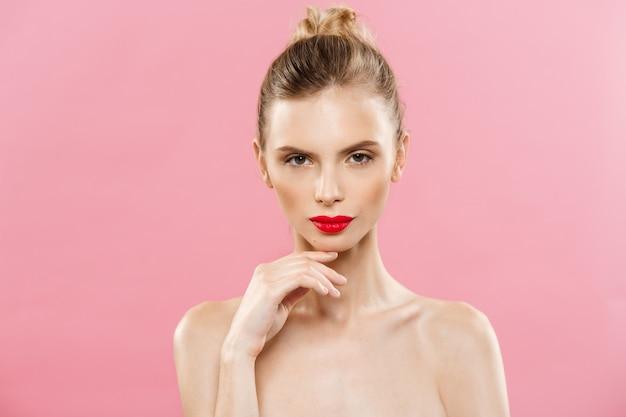 Concept de beauté - gros plan portrait de jeune femme brune jeune femme. beauty model girl aux sourcils brillants, maquillage parfait, lèvres rouges, toucher son visage. isolé sur fond rose