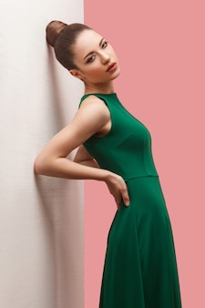 Concept de beauté de jeune beau modèle féminin en robe verte sur fond rose