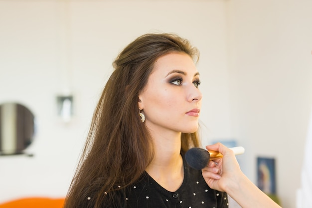 Concept de beauté et de maquillage - portrait en gros plan d'une belle femme se maquiller professionnellement avec un pinceau.