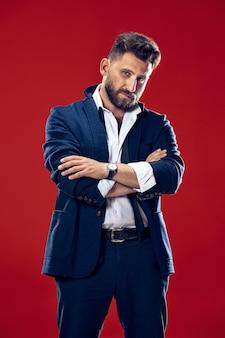 Concept de beauté masculine. portrait d'un jeune homme à la mode avec une coupe de cheveux élégante portant un costume tendance posant sur le rouge. cheveux parfaits