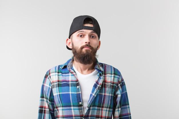 Concept de beauté, de mode et de personnes - portrait d'un jeune homme élégant hipster barbu sur blanc