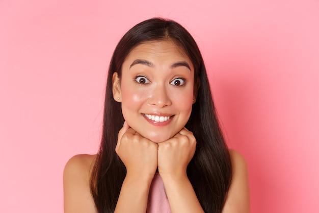Concept de beauté, mode et style de vie. gros plan, optimiste et excité, belle fille asiatique veut entendre l'histoire, anticipant, mur rose