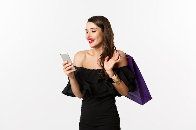 Concept de beauté et de shopping. superbe femme en robe noire élégante et maquillage, commande en ligne sur smartphone, sac tenant et souriant, debout sur fond blanc.
