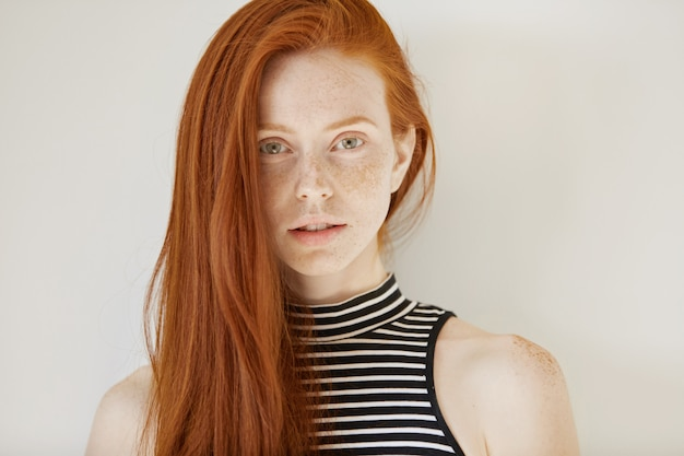 Concept de beauté et de soins capillaires. superbe jeune femme rousse de race blanche avec une longue coiffure lâche et des taches de rousseur portant un haut rayé sans manches, à la recherche réfléchie et pensive