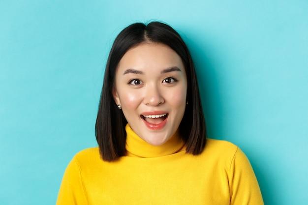 Concept de beauté et de soins de la peau. gros plan d'une femme asiatique surprise, élever les sourcils et regarder amusé à la caméra