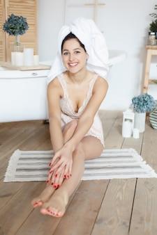 Concept de beauté, de soins de la peau et de personnes - beauté brune portant une serviette blanche venant juste de la salle de bain. bain de guérison, hydrothérapie, essayant de réduire la tension globale dans le corps et l'esprit. femme souriante