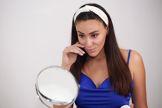 Concept de beauté, de soins de la peau et de personnes - souriante jeune femme en bandeau touchant son visage et à la recherche de miroir à la maison salle de bains