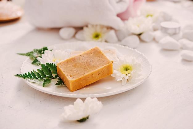 Concept de beauté, spa, soins du corps, bain et cosmétiques naturels - gros plan de barres de savon à la main sur tableau blanc