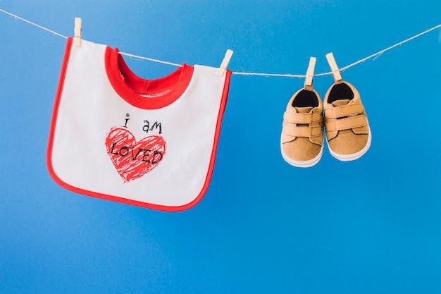 Concept bébé avec bavoir et chaussures sur le corde à linge