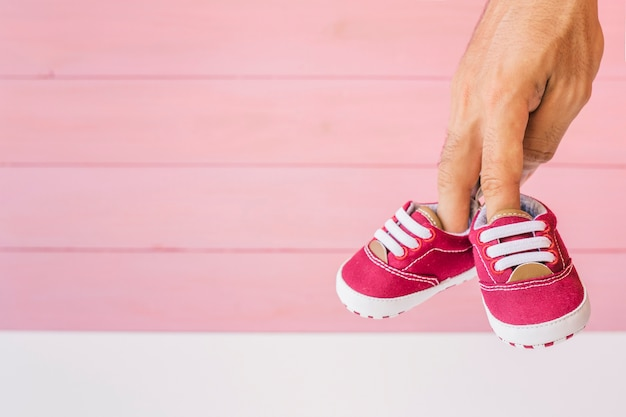Concept de bébé avec les doigts tenant des chaussures