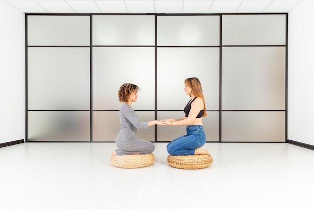 Concept de bien-être sain. méditation de deux femmes sur le sol. détendez-vous et zen dans la salle blanche. soin du corps.