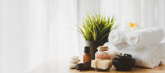 Concept de bien-être spa, pierre zen, bougie blanche, savon au lait, sel rose, serviette, fleurs et bouteille de massage à l'huile sur fond blanc table en bois