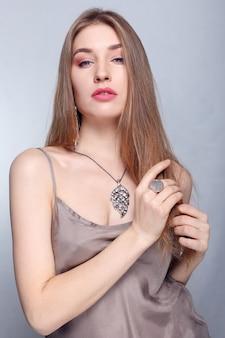 Concept de bijoux, vacances, luxe et personnes - beau visage féminin avec une peau parfaite et naturelle. peau de femme dorée. boucles d'oreilles, bague et collier en or. cosmétiques, beauté et manucure sur les ongles